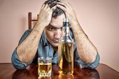 picture of alcohol abuse  - Drunk and depressed hispanic  man suffering a headache  - JPG