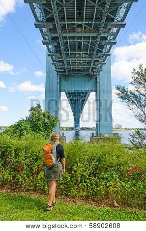 Young tourist looking at Verrazano-Narrows Bridge, NYC - view from Staten Island