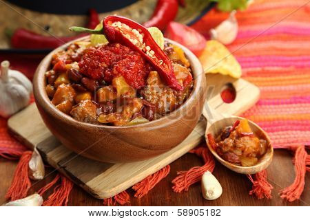 Chili Corn Carne - traditional mexican food, in wooden bowl, on napkin, on wooden background