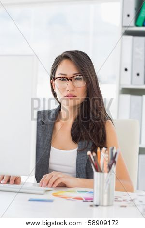Portrait of a serious young woman using computer in a bright office