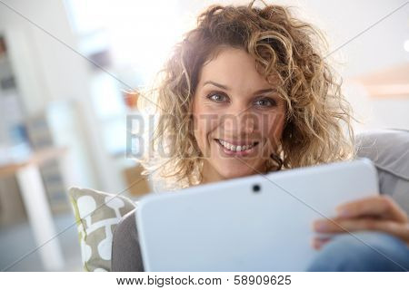 Smiling gorgeous woman websurfing on tablet