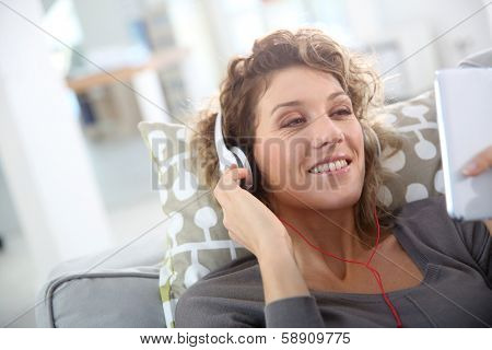 Smiling woman laying in couch and listening to music