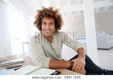Cheerful businessman sitting in home-office