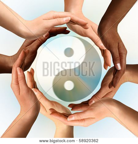 Conceptual yin-yang symbol with multiracial hands surrounding it. Balance, peace, meditation, spirituality concept.