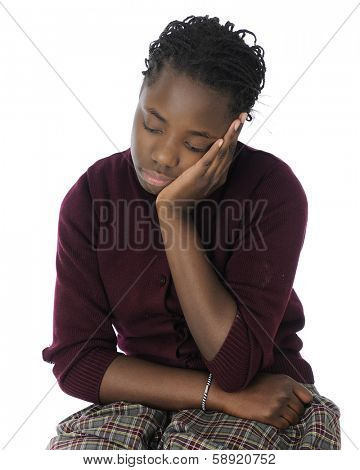 An attractive tween girl looking tired and bored in her school uniform.  On a white background.