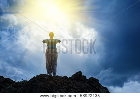 Woman standing on top of mountain doing yoga meditation. Stormy sky background, sun rays shining on her.