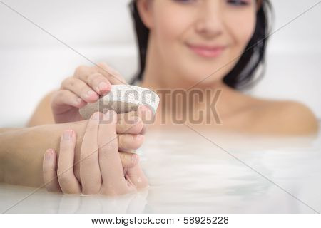 Woman Using A Pumice Stone To Exfoliate Her Feet