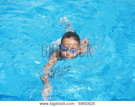 Little Girl Swimming with Goggles in a Swimming Pool