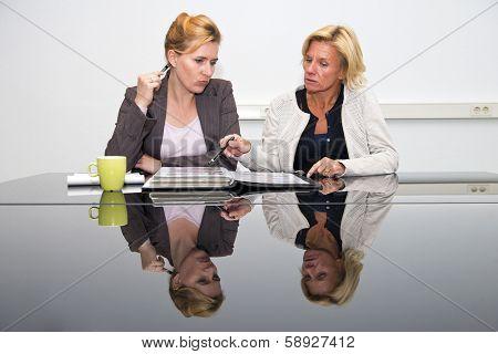 Two senior artdirectors, deliberating overa portfolio with design proposals