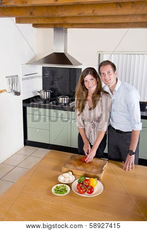 Young couple, coming home from work, standing in a spaceous kitchen, preparing dinner