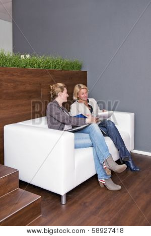 Two businesswomen going over notes together during an informal business meeting on a couch