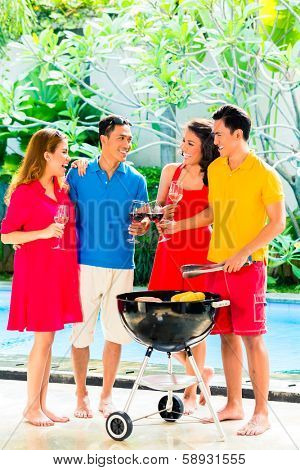 Asian friends having barbecue or BBQ at pool, drinking  wine and celebrating summer time