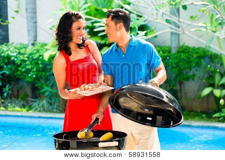 Asian handsome couple having barbecue party or BBQ outside at the pool with grilled corn cobs
