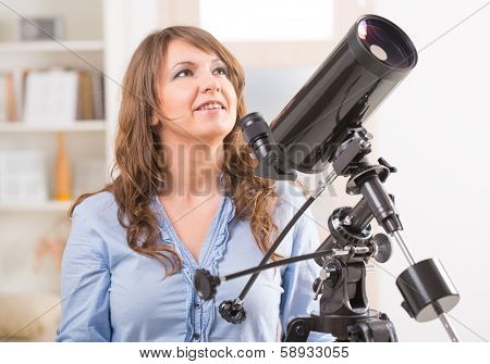 Beautiful woman looking skyward standing near a window with astronomical telescope