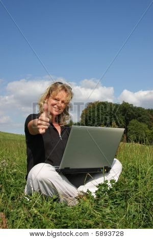 smiling woman with laptop posing with thumbs up sign