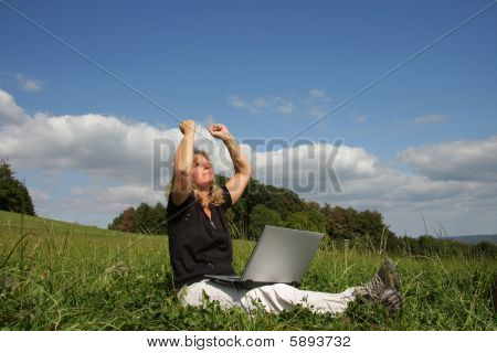 jubilating woman with laptop sitting in the meadow
