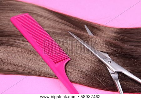 Long brown hair with comb and scissors on pink background