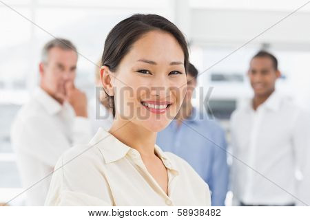 Happy asian businesswoman standing with team behind her in the office