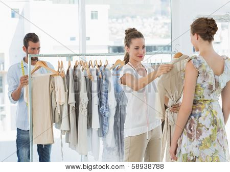 Female seller helping shopper choose the clothes in the store