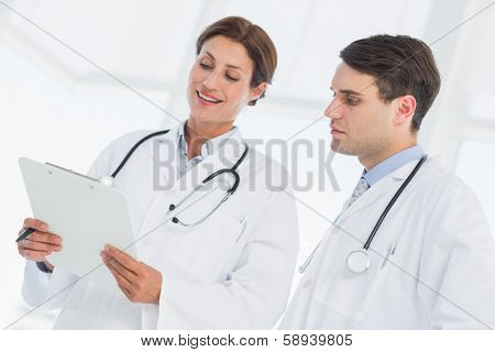 Male and female doctors looking at report in the hospital