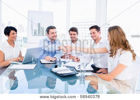 Smartly dressed executives shaking hands during a business meeting in the office