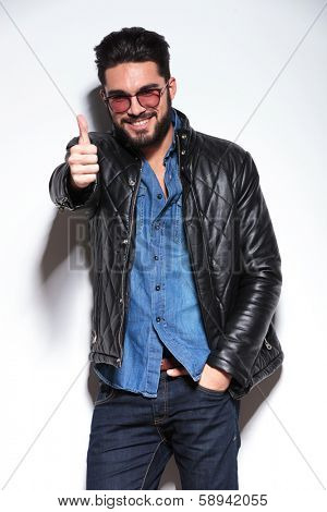 casual man in leather jacket making the ok thumbs up sign in studio