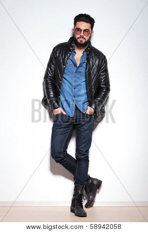 full body picture of a casual man in leather jacket, jeans and boots against studio wall