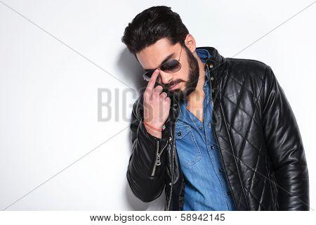 fashion man pushing his sunglasses back on , studio picture