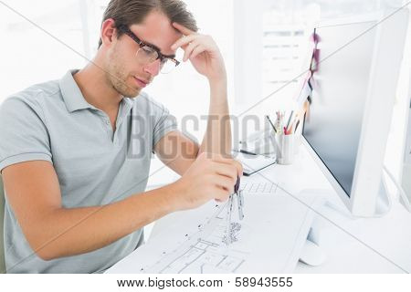 Concentrated young man using compass on design