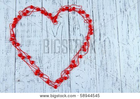 Heart-shaped beads on string on wooden background