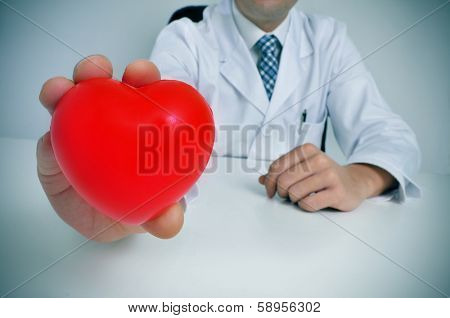a man wearing a white coat sitting in a desk showing a red heart