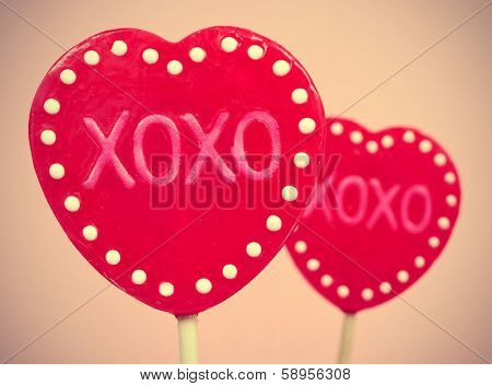 picture of some heart-shaped lollipops with the text XOXO, hugs and kisses, written in them, with a retro effect