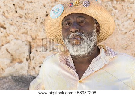 HAVANA,CUBA - JANUARY 20, 2014:Afrocuban man smoking a cigar near the Cathedral Square.Characters like this are common in Old Havana and a photo opportunity for the growing number of foreign tourists