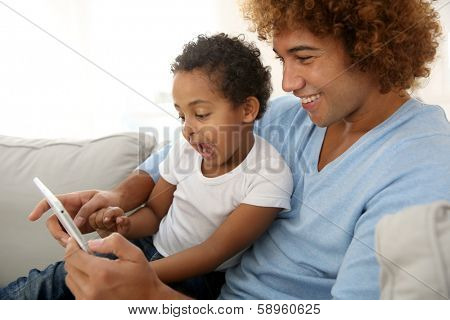 Father and child playing with digital tablet