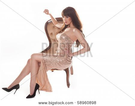 Beautiful elegant young brunette woman in a metallic gold evening dress and stilettos reclining gracefully on an antique chair isolated on white