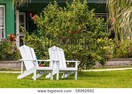 White Adirondack chairs in the home garden.