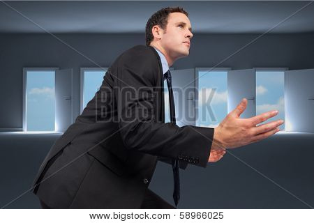 Businessman posing with arms out against doors opening in dark room to show sky
