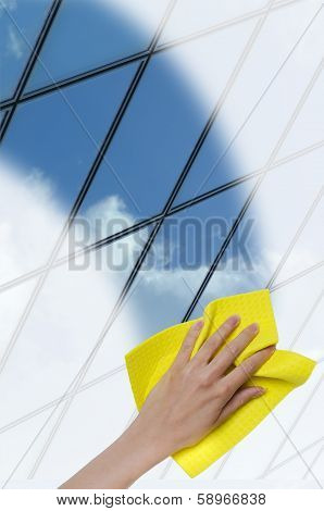 hand cleaning a glass surface of a building