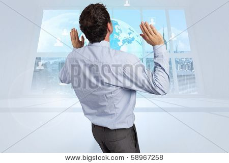Businessman standing with arms pushing up against server tower seen through window