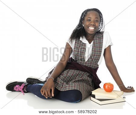 A happy tween girl relaxing on the floor in her school uniform, a small stack of books and an apple by her side.  On a white background.