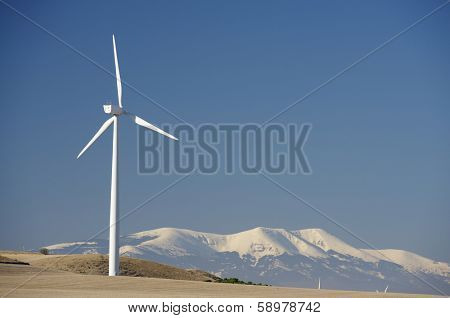 Windmills for renewable electric energy production, in the background is Moncayo Peak, Pozuelo de Aragon, Zaragoza, Aragon, Spain.