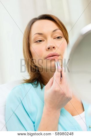 cosmetics and beauty concept - beautiful woman applying lipstick and holding mirror