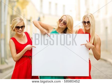 summer holidays, , travel, tourism and advertisement concept - three happy blonde women with blank white board in the city