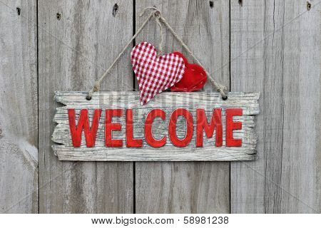 Red welcome sign with red hearts on wood background