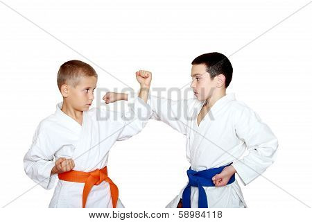 Children athletes in kimono perform techniques karate
