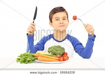 Young boy eating vegetables seated at table isolated on white background