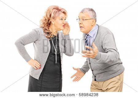 Mature lady whispering a secret to man isolated on white background