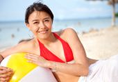 stock photo of beach holiday  - Woman at the beach leaning on a ball - JPG