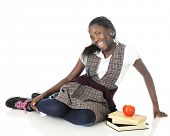 foto of tween  - An attractive tween girl looking happy but a bit shy as she relaxes on the floor with 3 books and an apple - JPG