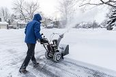 picture of blowers  - Man clearing snow with a gas snow blower - JPG